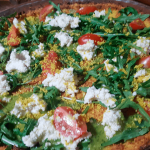 Pizza con base de coliflor al pesto, con queso vegano y rúcula